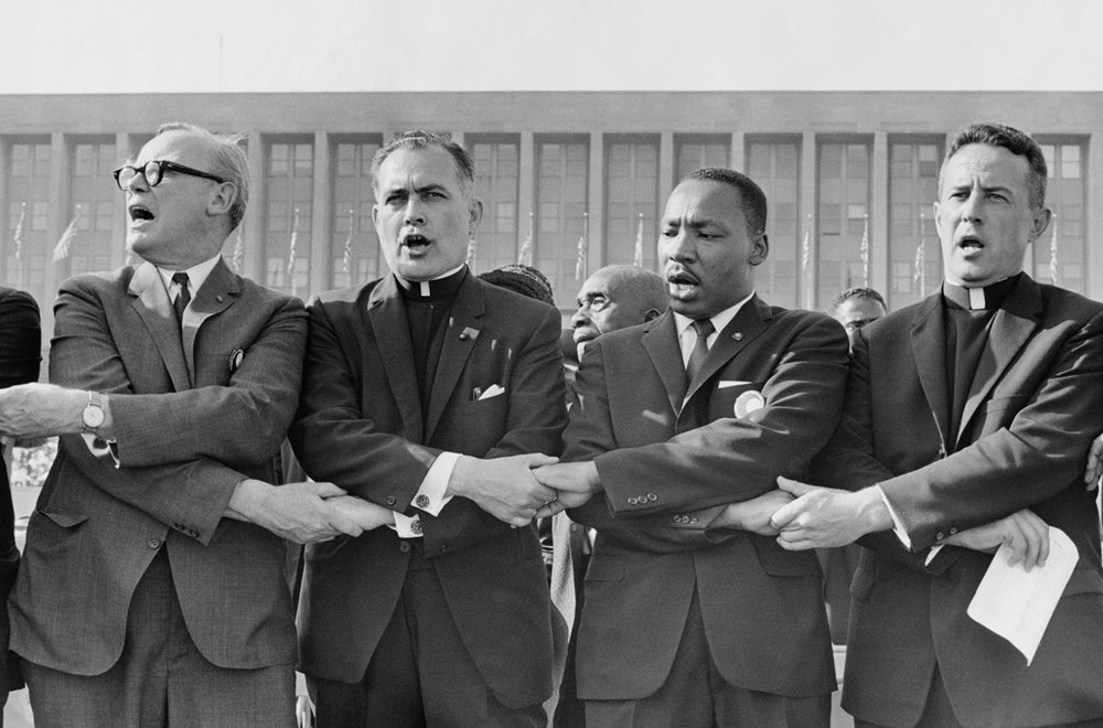 "Father Hesburgh together with Rev. Martin Luther King Jr., singing ""We Shall Overcome."""