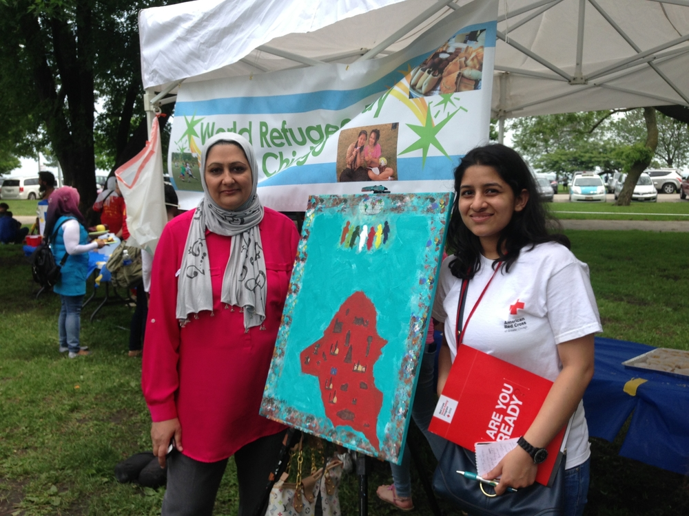 Red Cross volunteer, Amisha Sud, stands beside a painting by refugee Amal Alsandok.