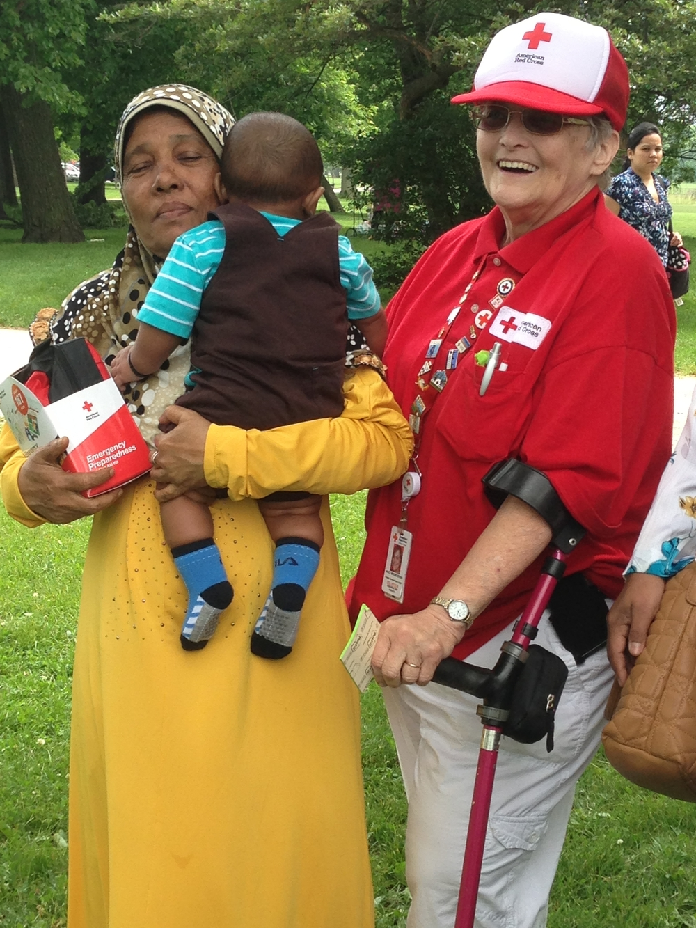 Red Cross Health Services volunteer, Nancy Brooks-Edison, with Haraj Gulbahar and her great-grandson from Malaysia.