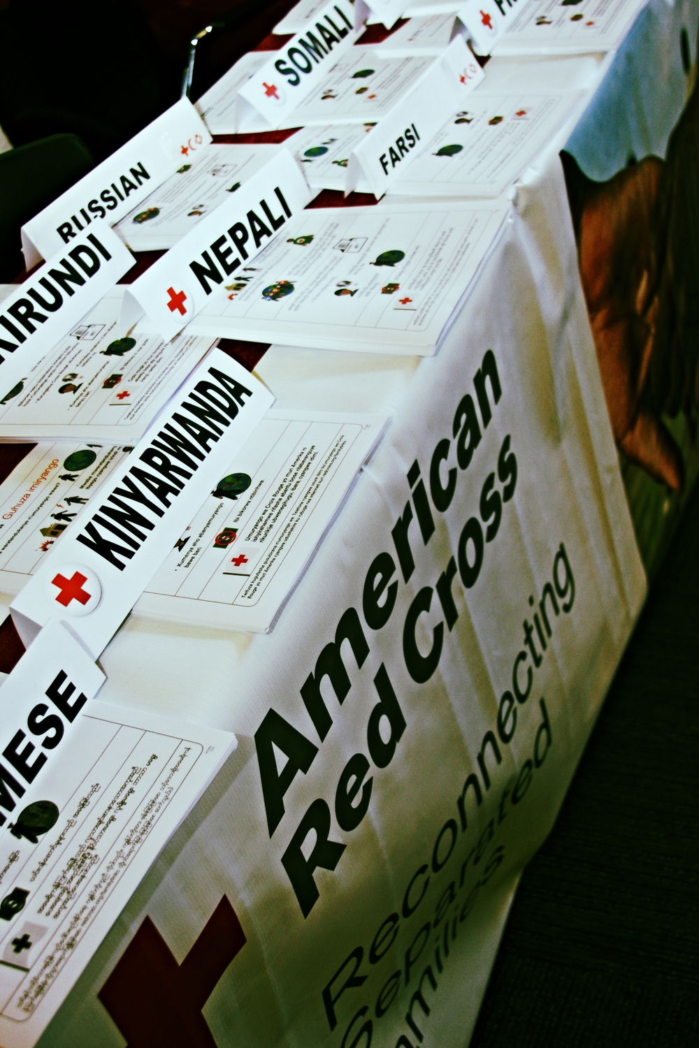 The Restoring Family Links resource table at World Refugee Day offered materials in many languages to help explain the services available to refugees through the American Red Cross.