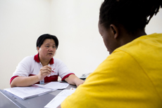 Lim Mei Chin, Malaysian Red Crescent's Restoring Family Links officer, helps Catherine write a message to her family in Uganda.