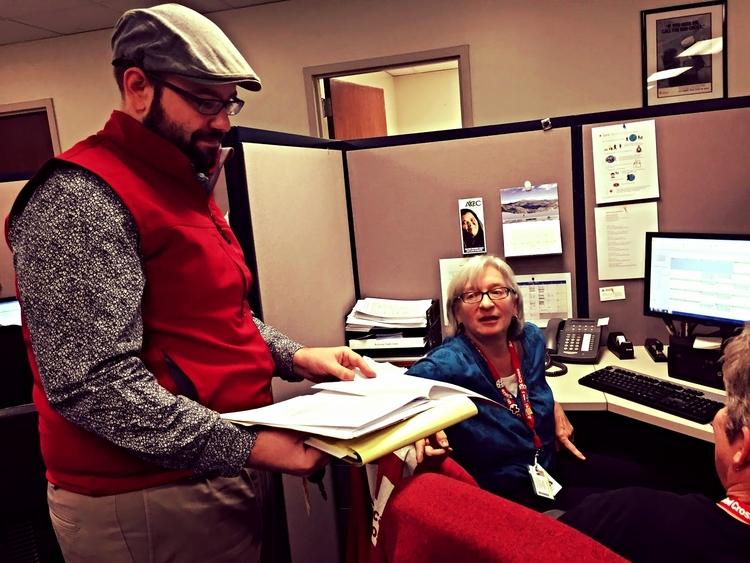 Tim y Robbe del equipo de Restablecimiento de Contacto Familiar revisan el caso, antes de entregar el mensaje.