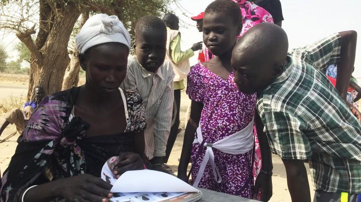 En la búsqueda de sus seres queridos, un grupo de personas en Leer revisan un libro lleno de fotografías de niños del Sur de Sudan que se encuentran en países vecinos. CC por-NC-ND/CICR/Pawel Krzysiek