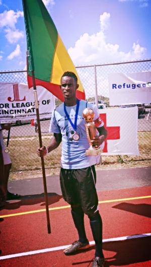 Uno de los ganadores de Ghana con el trofeo del equipo y la bandera