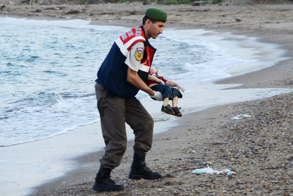 A Turkish officer carrying 3-year-old Aylan. Nilufer Demir/DHA, Reuters