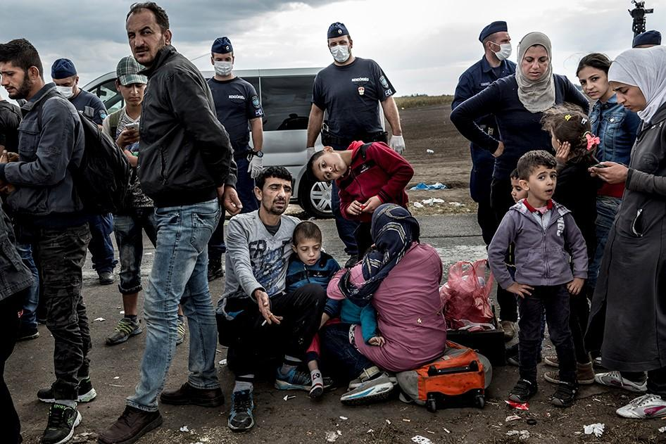 Asylum seekers and migrants with children wait at the Roszke collection center on the Hungarian border with Serbia, surrounded by Hungarian police, to board buses to temporary detention centers. Roszke, Hungary. September 8, 2015. Zalmaï/Human Rights Watch