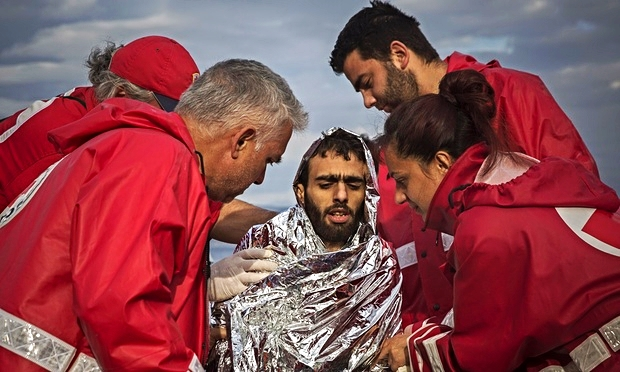 Members of the Greek Red Cross help a refugee who has just landed on a shore at Lesbos. Credit: Santi Palacios/AP