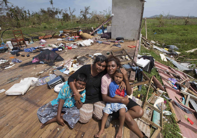 Sanjogeeta Kiran, right, with her sister Sulva Kiran, second left, and her children Shivendera, left, and Raajeen, sit amid the debris of their home in RakiRaki, Fiji. Photo credit: AP