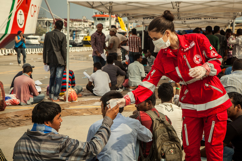 Red Cross volunteer gives water to newly arrived migrant in Italy, Jully 2015 (Photo: International Federation of Red Cross and Red Crescent Societies)