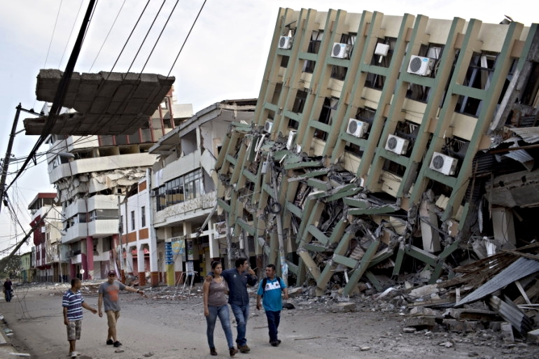 Residents walk Monday past a row of buildings felled by Saturday night's 7.8-magnitude earthquake in Portoviejo, Ecuador. Photo credit: Rodrigo Abd, Associated Press
