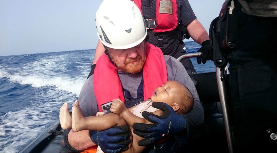 A Sea-Watch crew member holding a drowned baby after a wooden boat transporting migrants capsized off the Libyan coast on May 27, 2016. Photo Credit: Christian Buttner / AFP