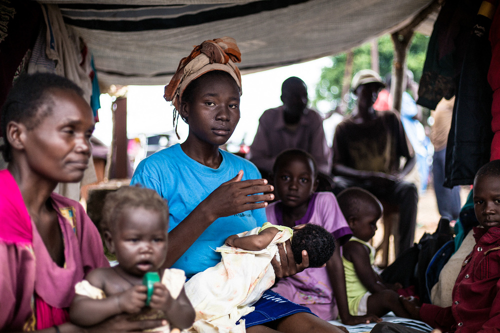 Biringi, outside the town of Wau, South Sudan.   Women waiting to receive food from the ICRC at the Biringi displacement site approximately 25 kilometres from Wau. Within a week following the armed clashes, the ICRC had distributed food rations to some 70,000 people.