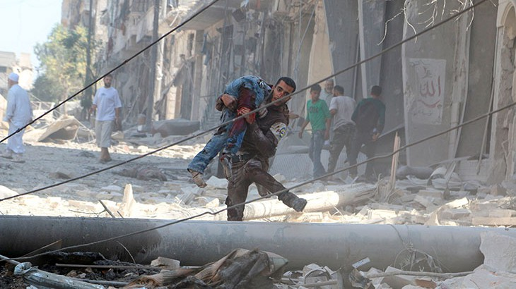 A man carries an injured person amid rubble of damaged buildings in Aleppo, Syria. Photo Credit: Abdalrhman Ismail, Reuters