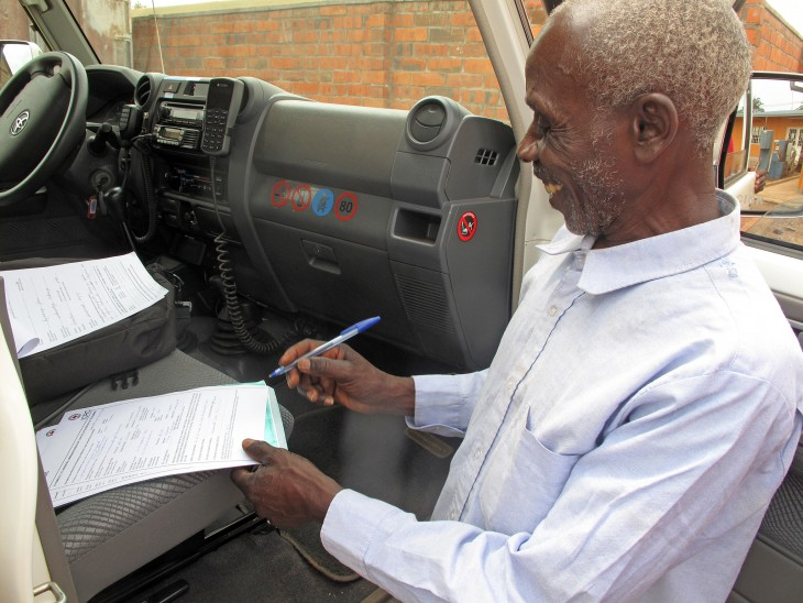Rwanda. Raymond's father signs the handover certificate for his son. CC BY-NC-ND / ICRC / Emmanuel Nyandwi