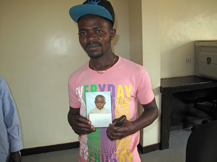 Rwanda. Raymond displays a photo of himself taken in 1994, shortly after the Rwandan genocide separated him from his family. CC BY-NC-ND / ICRC / Emmanuel Nyandwi