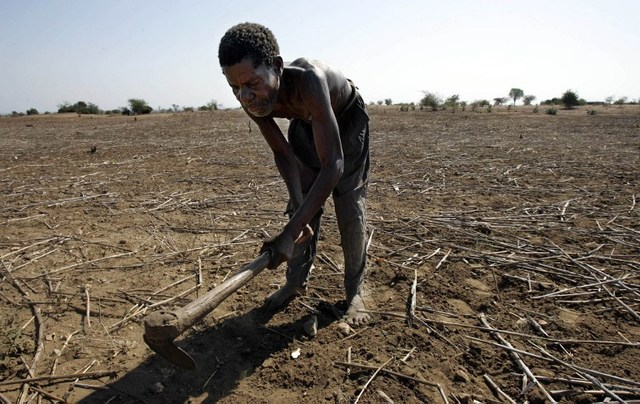 Farmer works on land affected by drought. Photo Credit:Gianluigi Guercia/AFP