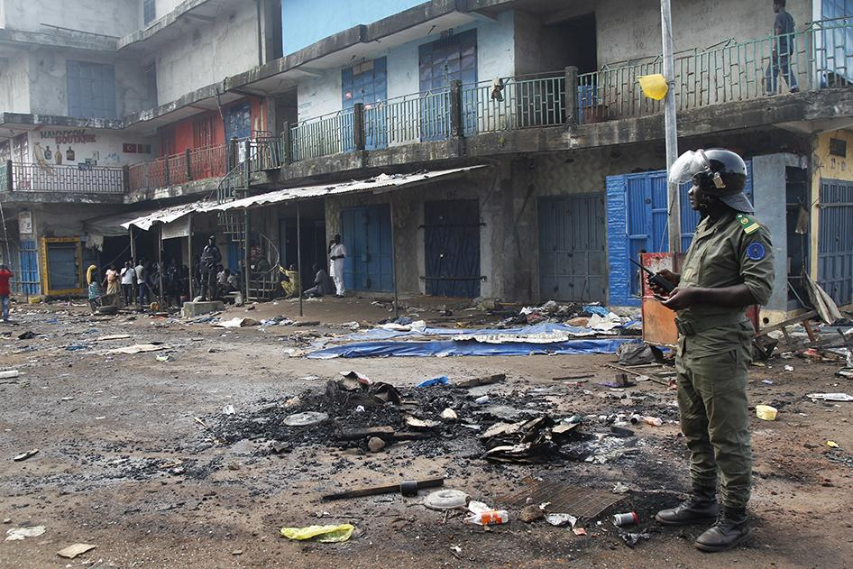 Officer stands outside Madina Market in Conakry, Guinea following election violence. Photo Credit: Reuters