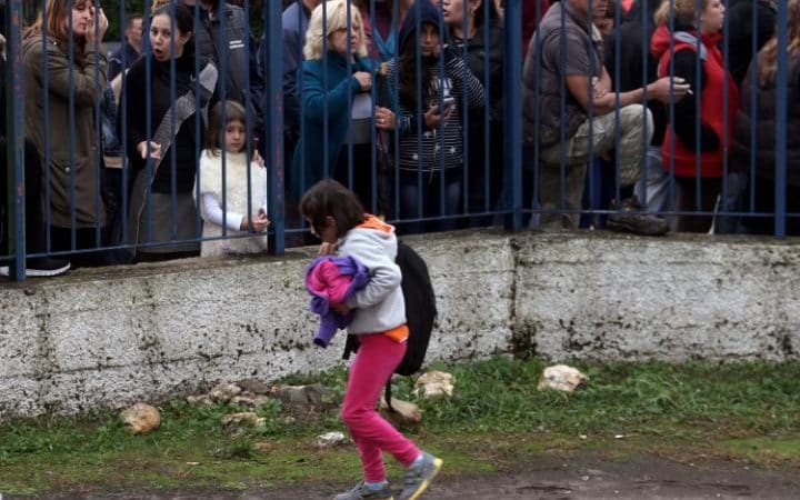 Refugee child stands outside primary school locked by Greek parents. Photo Credit: Saskis Mitrolidis/AFP