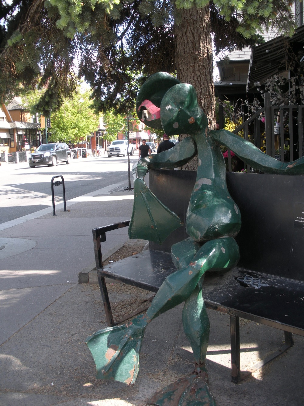 """Hanging Out"" by Peter Smith (1994). Three frogs used to sit on this bench on the corner of Fourth Street and 21st Avenue SW. The day I visited, there was only one. Anyone know what happened to the others? (Photo: Shaun Hunter)"