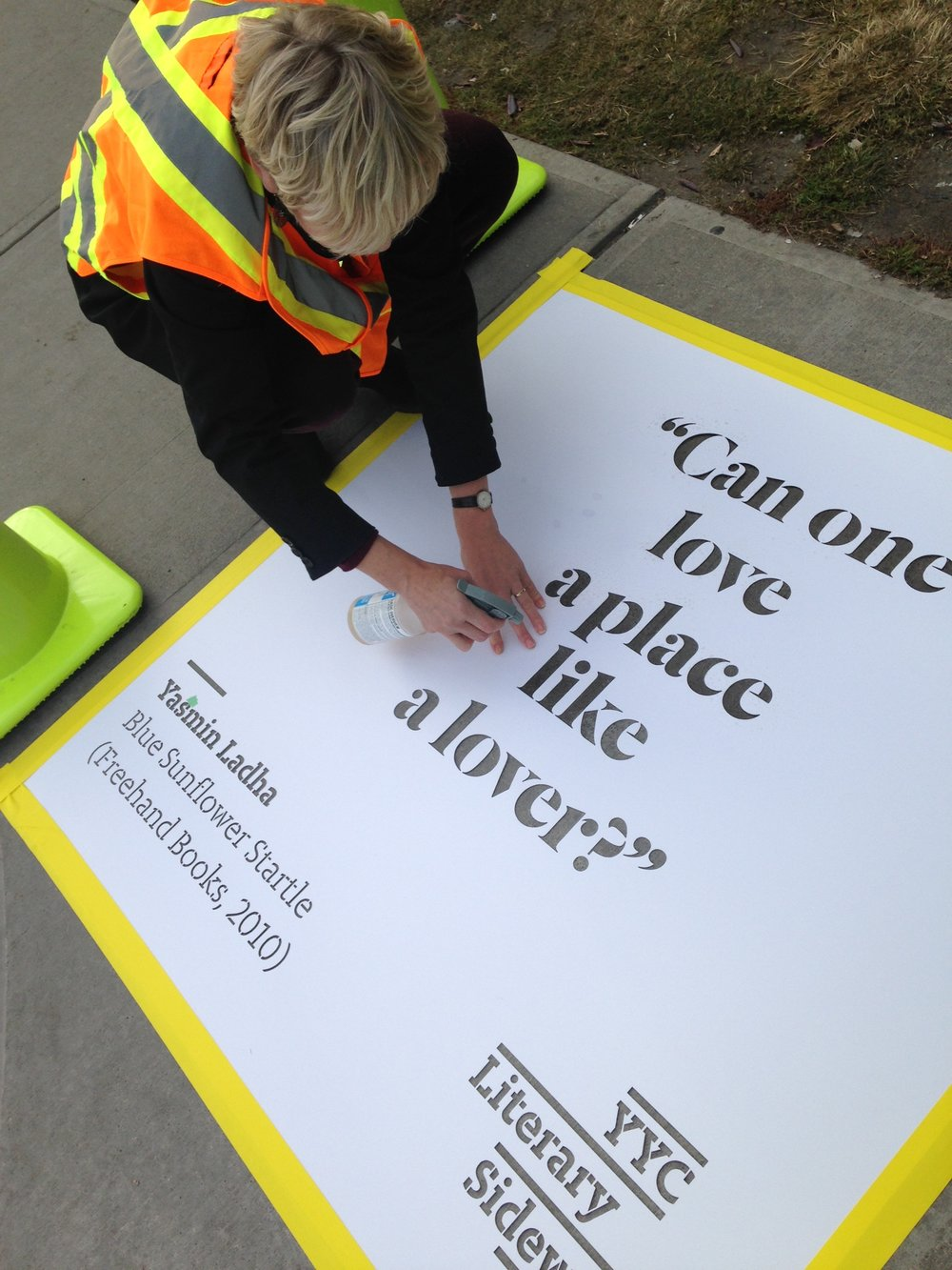 Rosemary Griebel (Calgary Public Library) sprays a quote from Yasmin Ladha's Blue Sunflower in front of the Crowfoot Library.