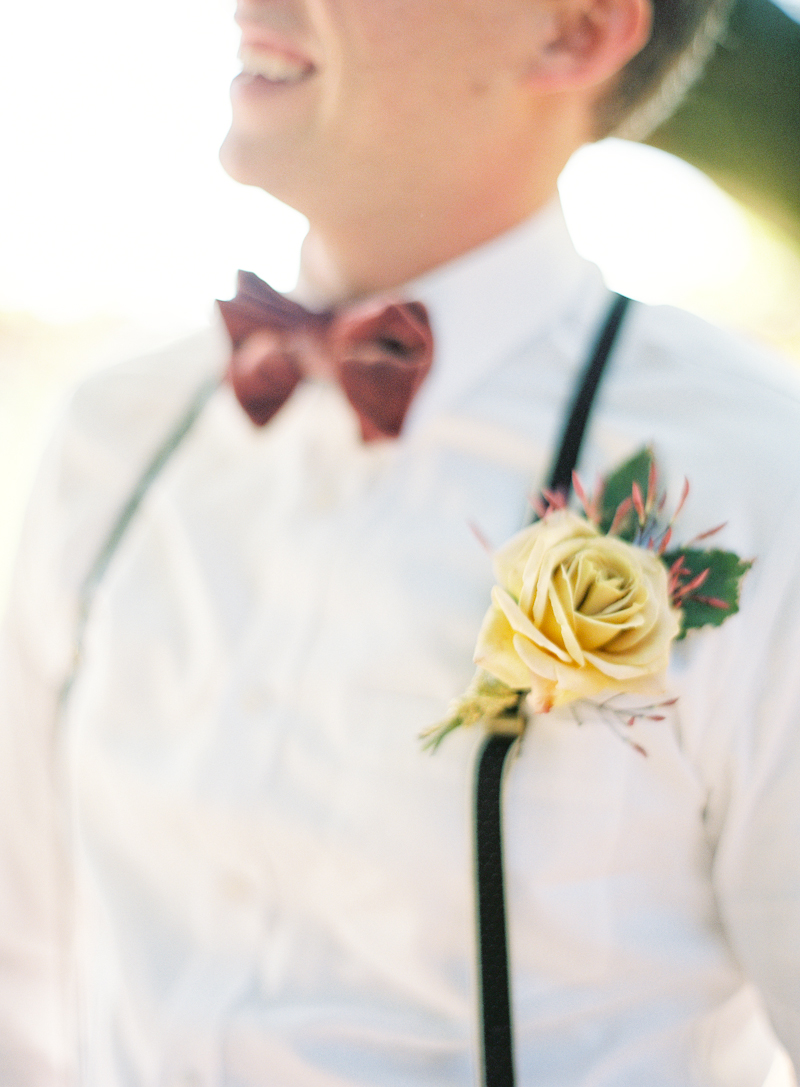 groom's yellow boutonniere and red bow tie