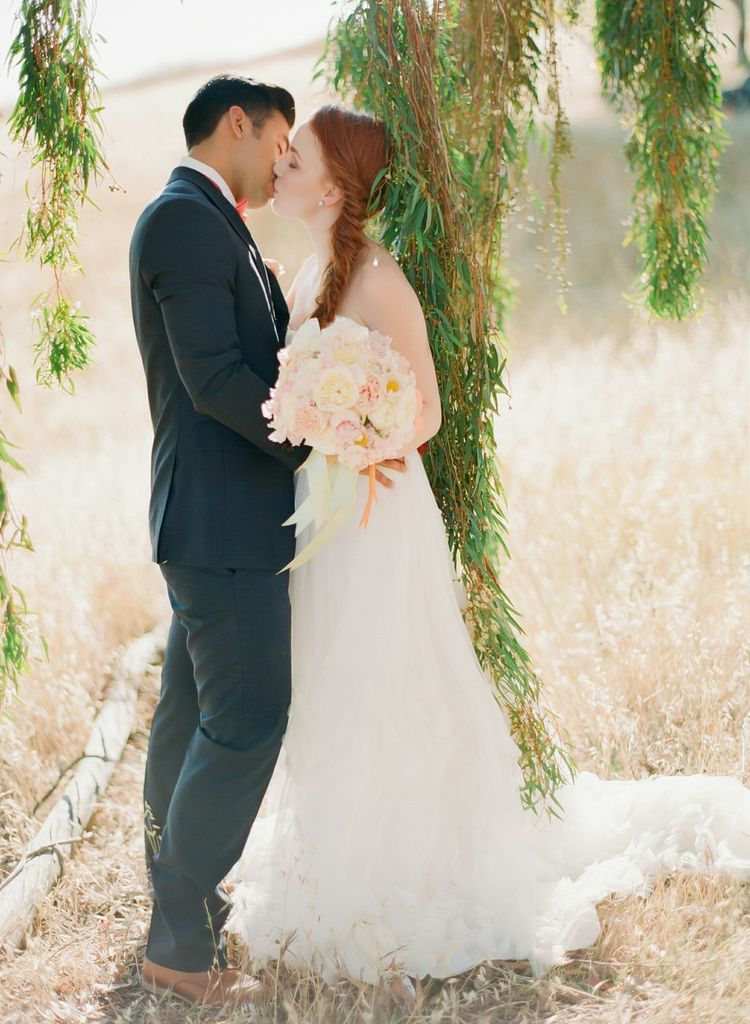 bride and groom standing in a field, bride holding bouquet designed by chandara creative, photo featured on Style Me Pretty
