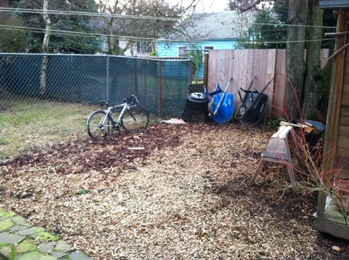 Wood chips are the best solution that I have found for areas that are in a holding pattern. Weeds don't grow well in in them, because the chips are stealing all of  the nitrogen to break themselves down.