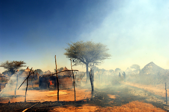 2005 - The village of Tama, Sudan, burning. Photo: Lynsey Addario.