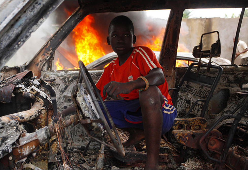 A Christian youth squats inside a burnt-out car in Bangui - Photograph: Emmanuel Braun/Reuters; Source: The Guardian