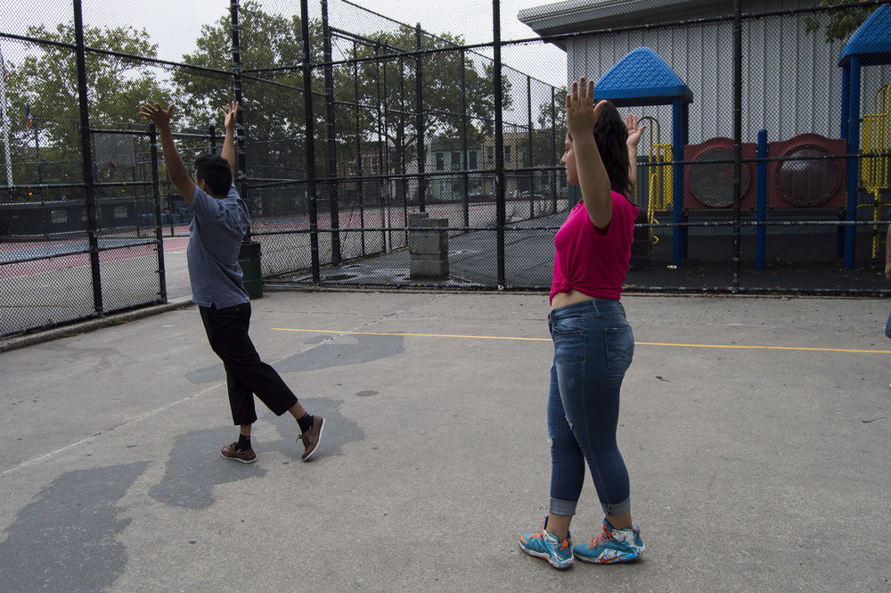 Benito Bravo shows the quinceñera how to hold her arms. Gabrielle Narcisse and Deleelah Saleh for Picture Justice. August 17th, 2017, Brooklyn, Hena Perrera Park, 47th and 4th ave.
