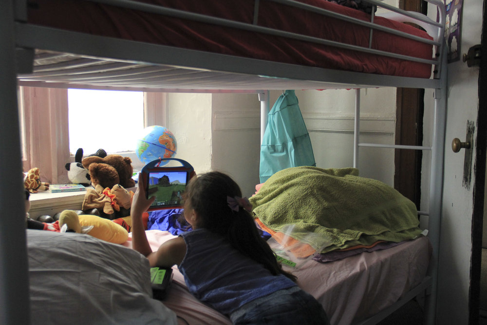 Gabriela (8) explores her fantasy world through Minecraft in which she built her two-story house next to a lake and trees. Dulce works on her own tablet, modeling Minecraft universe after her new home in the church.Holyrood Episcopal Church in Washington Heights, New York. August 17, 2017.