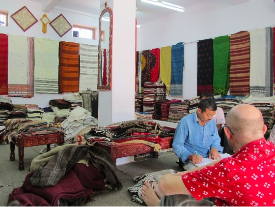 Doing business, surrounded by Vankar Vishram Valji handiwork.