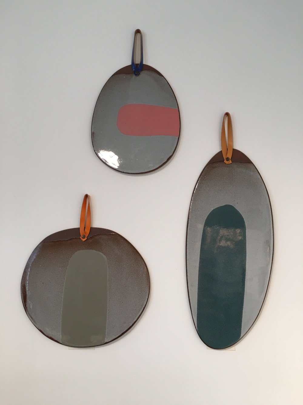 Slovakian ceramicist Silvia K's tin-glazed earthenware platters with leather detailing.