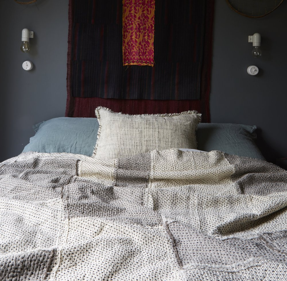 A Stitch by Stitch Raw Chindi Quilt adds light and texture to this bedroom with dark grey green walls