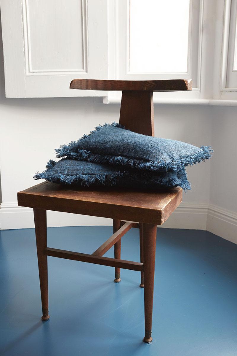 Desi Indigo handwoven wool cushions sit on an unusual chair found at a flea market