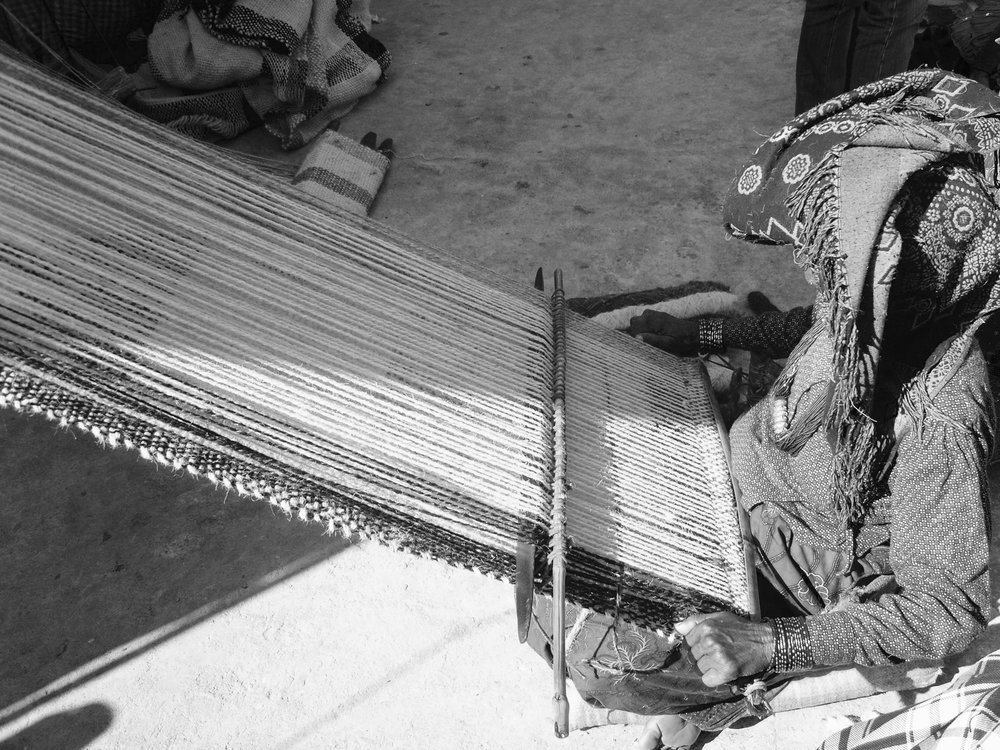 A weaver working on a traditional nomadic back-strap loom