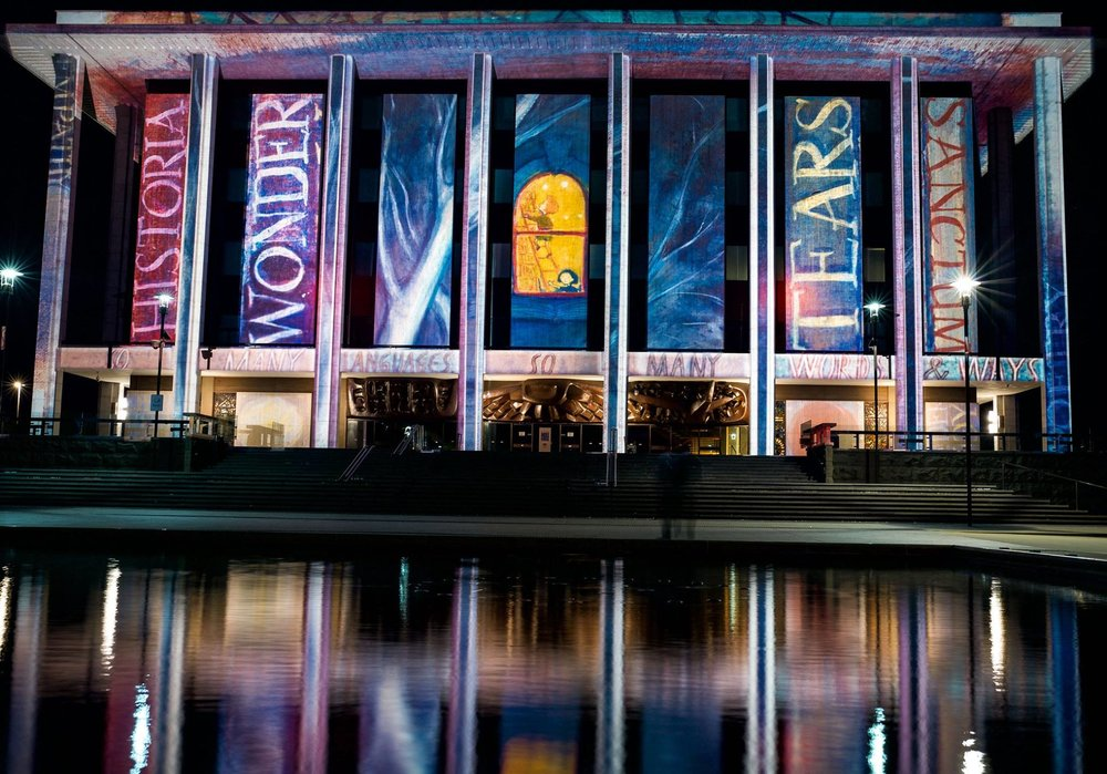 """A projection at the National Library of Australia of """"Midnight at the LIbrary"""" by Ursula Dubosarsky, illustrated by Ron Brooks, as part of the Enlighten Festival 2019."""