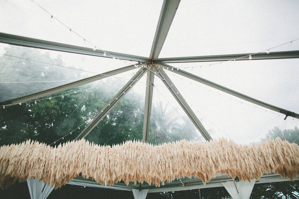 The pampas grass chandelier spanned 32' above the head table at Amber Mozo's wedding. It was the perfect focal point for this chic wedding set among the beach cottages of Hawaii's North Shore.