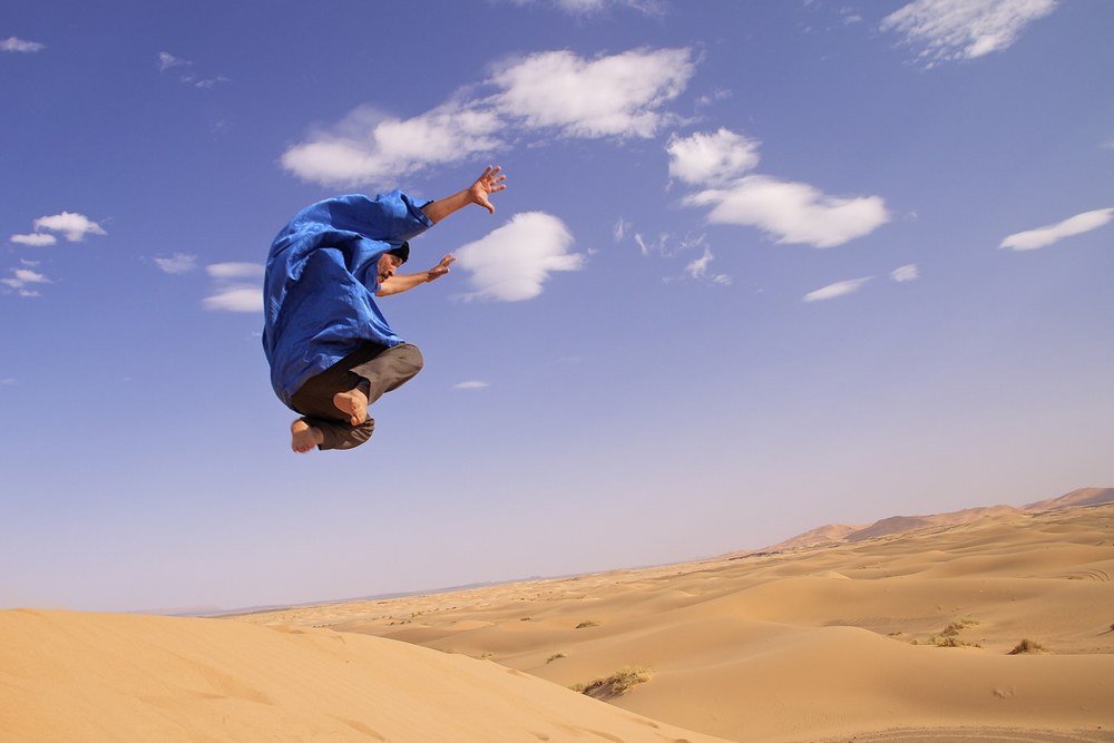 Moh saltando desde lo alto de una duna en medio del Sahara .