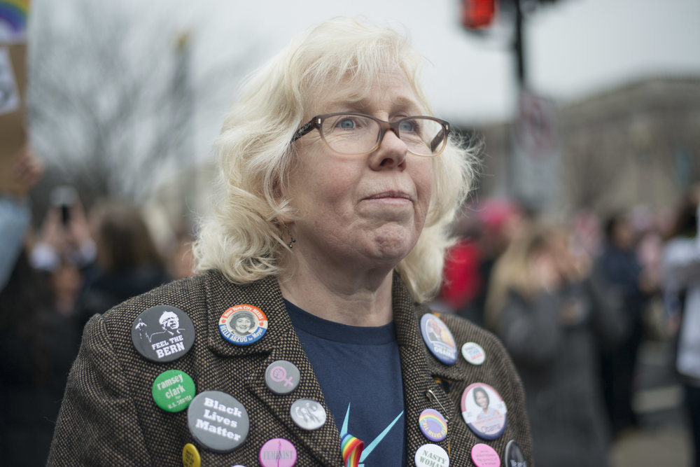 A woman looks on during the Women's March on Washington. 2017