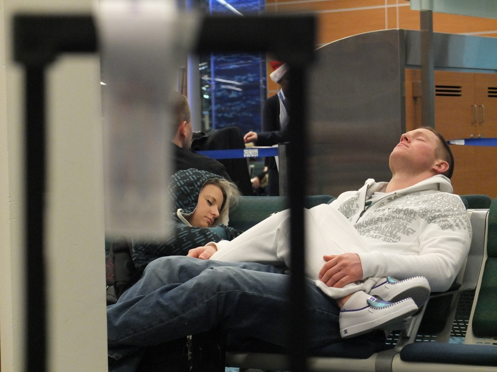 An exhausted young couple falls asleep on an airport bench.  Fuji X10 at 28mm at f2.8 1/110 ISO 1250