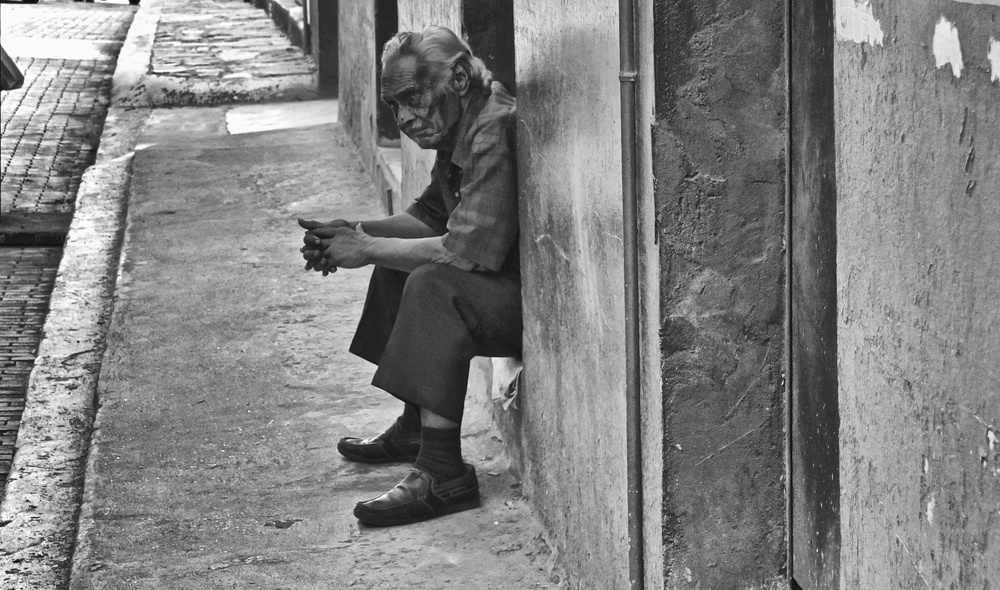 An old man, the years written on his face, waits and watches in the street. Fuji X10 at 28mm 1/180 f/5 ISO 200 −1.33ev