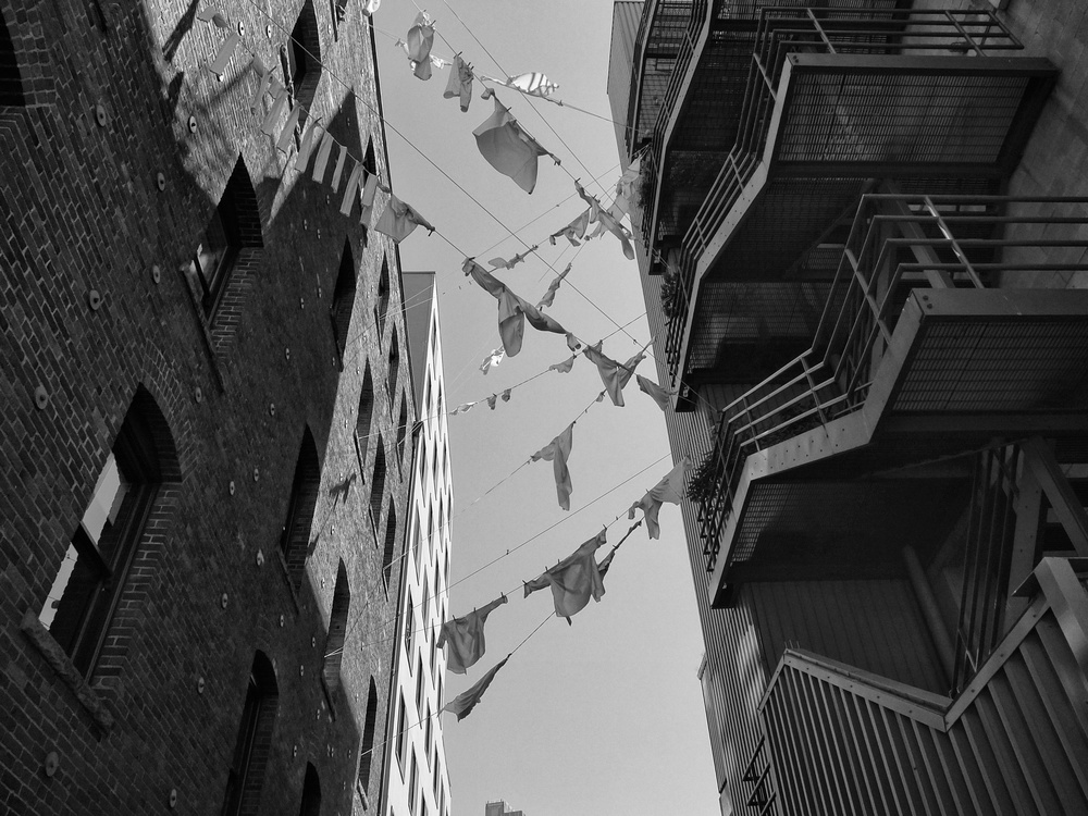 Laundry flies in the blue sky over a Seattle alley.  Fuji X10 at 7mm F/6.4 1/500 ISO 200 -1e