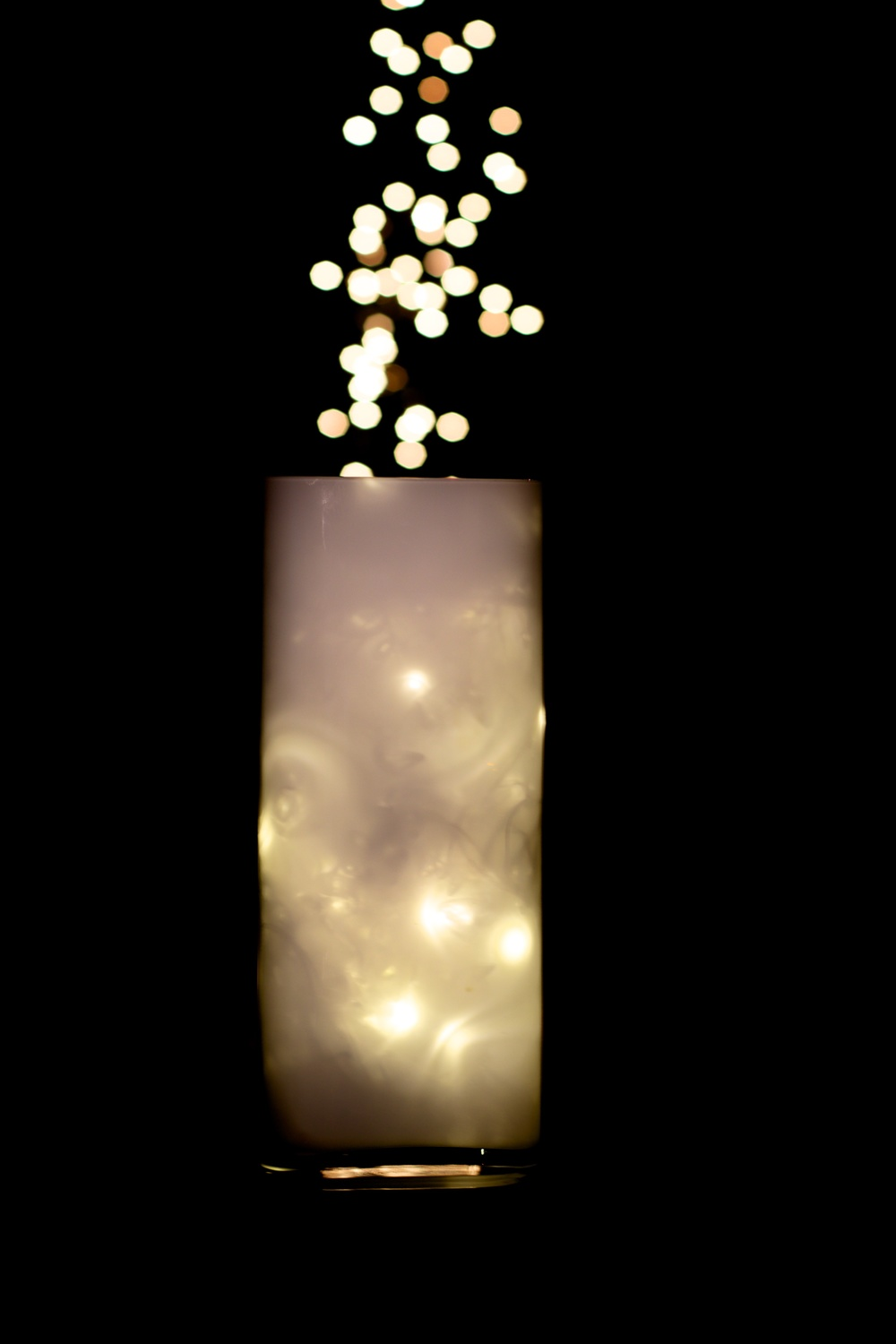 Bubbles of light drift up out a luminous glass vase.  Canon 7D Mark ii EF 50mm 1.4 at f2.8 1/13 ISO 100