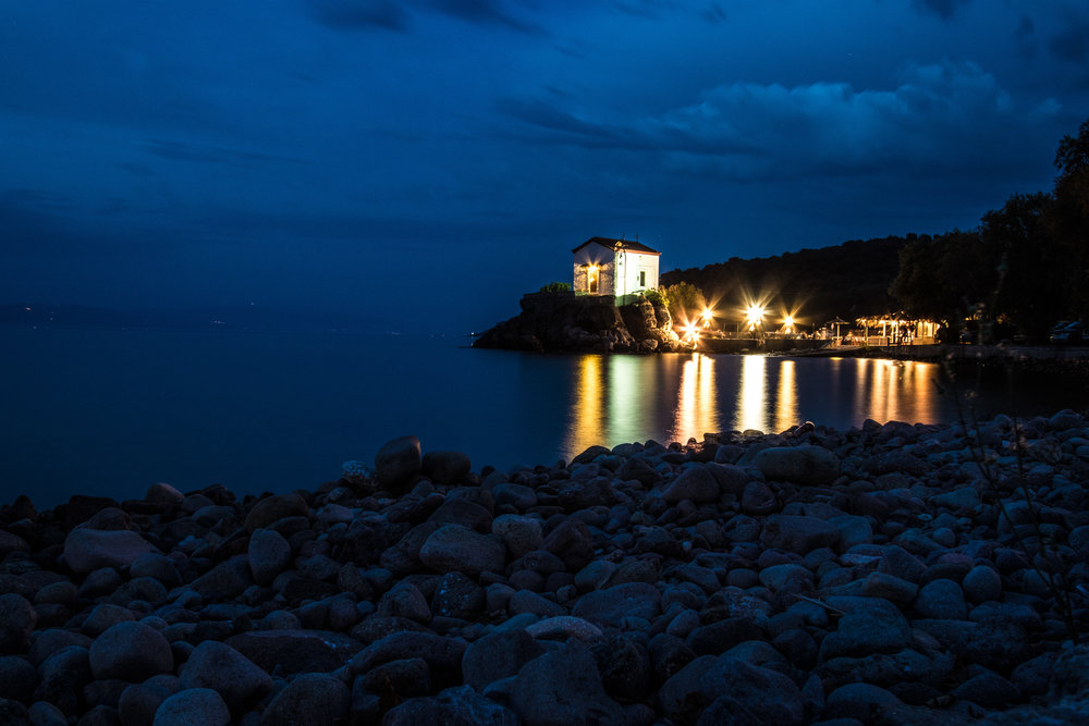 The warm lights of the church at Skala Sykamineas on Lesvos draw us on into the blue twilight.  Canon 7D Mk ii EF-S 10-22mm at f/13 30 sec ISO 200