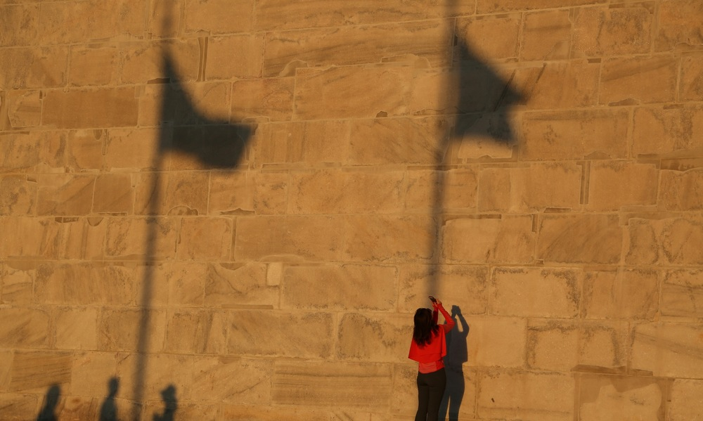 A woman in red takes a picture of the Washington Monument with her cell phone on October 8, 2014. Visitors congregate around the monument as the sun sets in Washington, D.C.