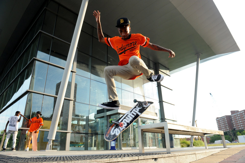 "Jamal Cottman, 20, does a trick in front of the Baltimore Visitor Center in the Inner Harbor. Cottman is a member of a skating crew called '""Milk Squad."""