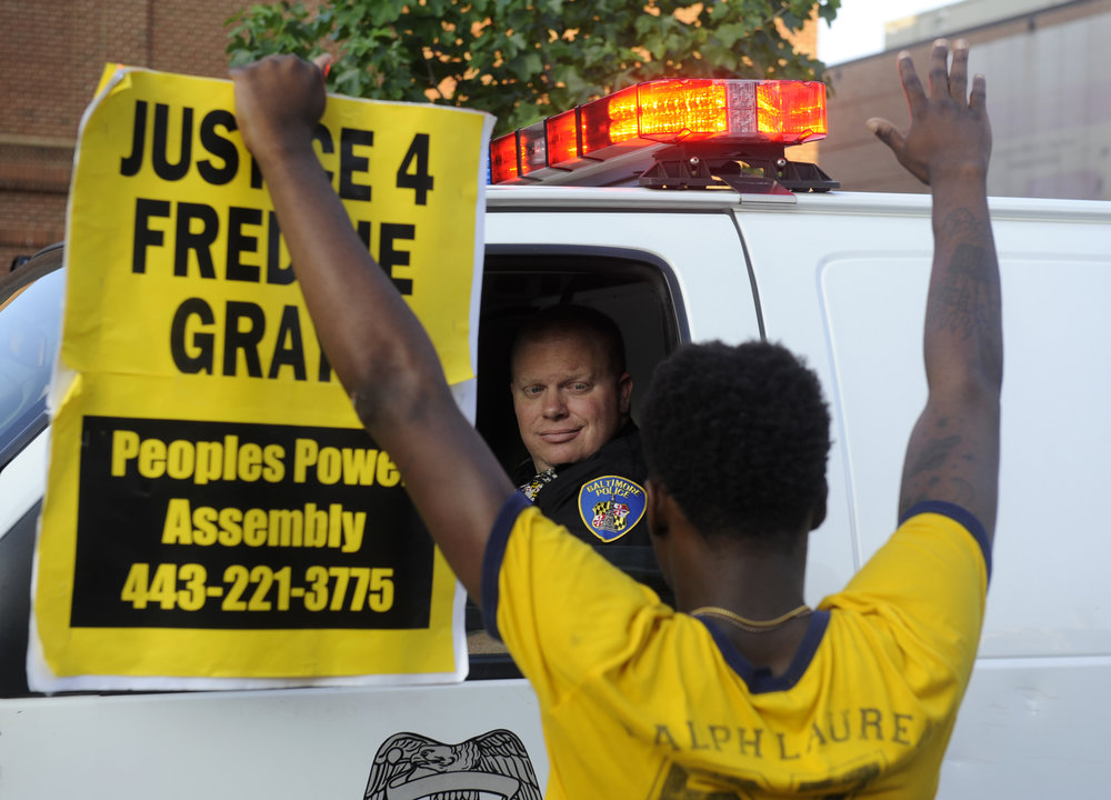 "Melvin Townes of West Baltimore stands with a ""Justice 4 Freddie Gray"" sign in front of a police officer. Protestors gather at McKeldin Square in Baltimore Friday, July 8, 2016, and march to protest the deaths of Alton Sterling and Philando Castile."