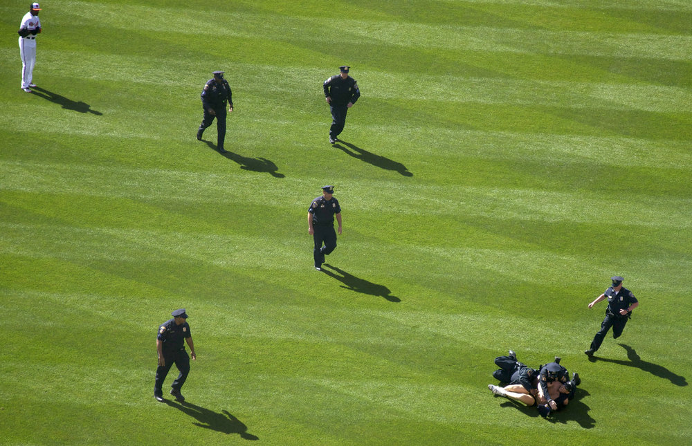 Mark Harvey of Severn, Maryland, is pinned down by police after running across the Camden Yards field during the Baltimore Orioles Opening Day in April 2012.