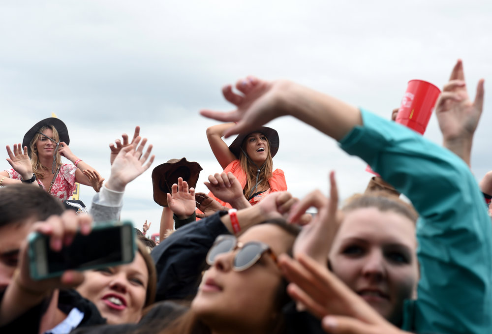 Fans listen as Fetty Wap performs during the Preakness Stakes' InfieldFest Saturday, May 21, 2016 in Baltimore, Maryland.